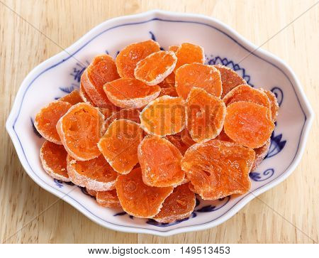 Dried candied fruits kumquats in porcelain bowl.