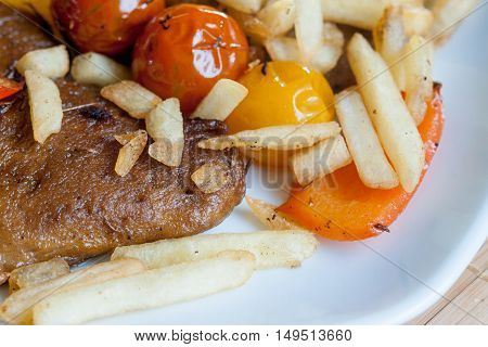 Vegetarian steak made from vegan meat - seitan with cherry tomatoes sauce and fries.