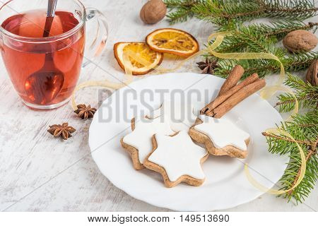 Close up of homemade butter nuts star shaped cookies with icing pine orange slicescinnamon anise walnuts and golden ribbon over white wood background. A cup of berry tea. Christmas decoration.