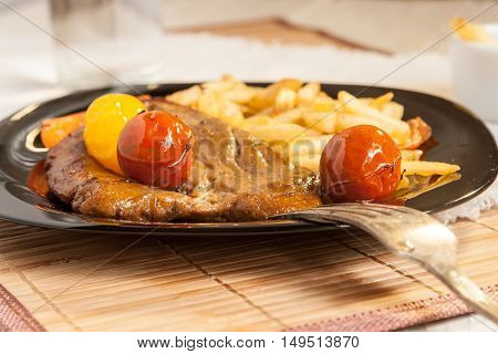 Vegetarian steak made from vegan meat - seitan with cherry tomatoes and fries on black plate