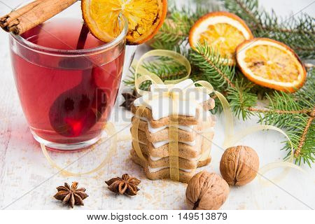 Homemade butter nuts star shaped cookies with icing pine orange slicescinnamon anise walnuts and golden ribbon over white wood background. A cup of berry tea. Christmas decoration.