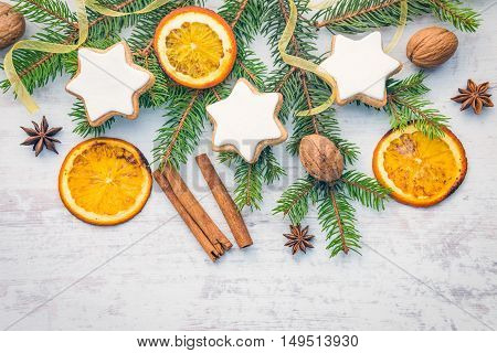 Christmas decoration over white wood background. Top view of homemade butter nuts star shaped cookies with icing pine orange slicescinnamon anise walnuts and white ribbon