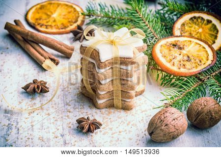 Close up of homemade butter nuts star shaped cookies with icing pine orange slicescinnamon anise walnuts and golden ribbon over white wood background. Christmas decoration.