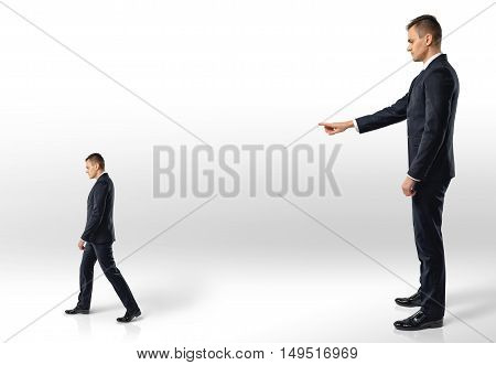 Businessman points at another man following in the direction indicated. Reproach and remark. Superiors and subordinates. Losing a job.