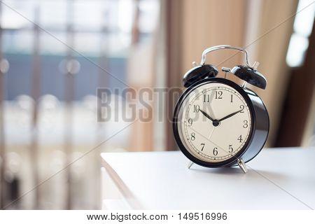 A black alarm clock on the nightstand