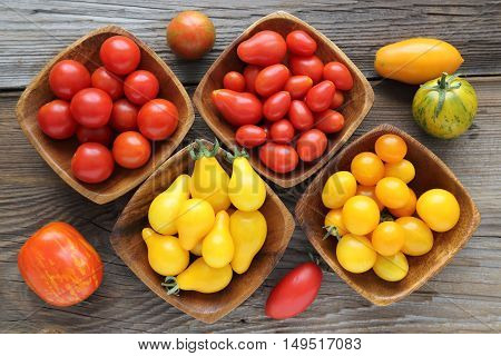 Colorful different kind tomatoes in wooden bowls.