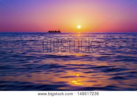 Evening seascape. Silhouette of man on the boat against the setting sun. The sun reflected off the waves. Purple pink and yellow colors