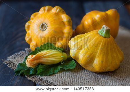 three yellow pattypan squash with leaf and flower on a dark wooden table.