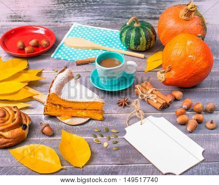 A piece of pumpkin pie with a cup of coffee among autumn attributes: acorns hazelnut and yellow leaves.