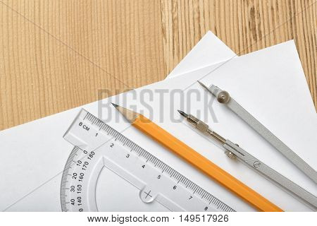 Layout with protractor, pencil and compass on white paper which is on wooden surface. Top view composition. Engineering stuff. Work place of draftsman, architect, constructor. Construction and architecture. Measurement.