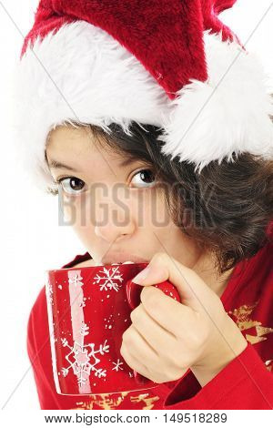 Close-up image of a young teen girl sipping cocoa with marshmallows in a red mug.  She's wearing a Santa hat and red pajamas.  On a white background.