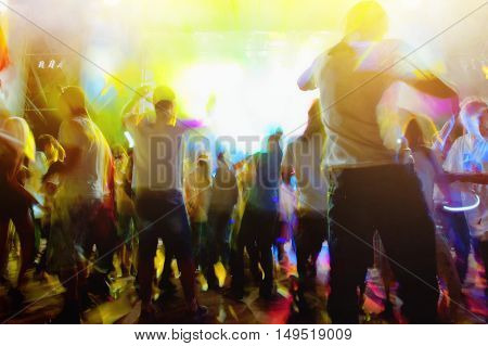young people dancing and having fun at night disco blurred background