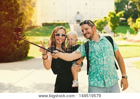 Young Family Making Selfie Photo On Motion Camera In Park Of Europe