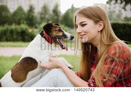 young pretty girl in red tartan shirt and jeans sit at the lawn near high buildings and kiss her dog. Love and friendship concept. Profile view close up portrait.