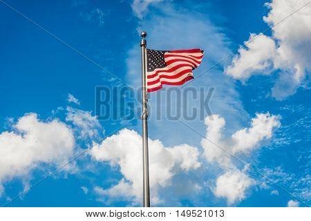 The American flag waving in the wind with a blue sky with puffy clouds background.