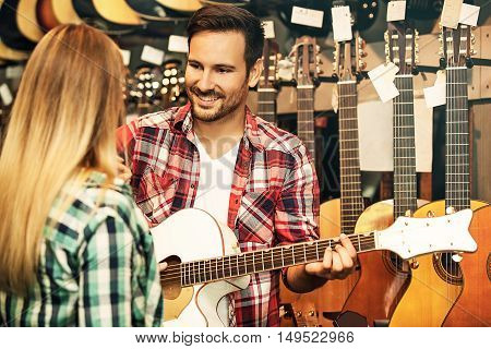 Young salesperson is showing to woman how to play guitar.