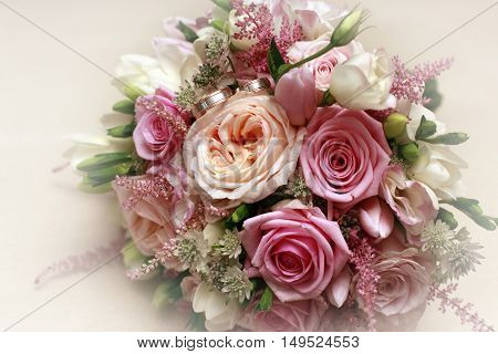 Beautiful wedding bouquet from pink roses and wedding ring