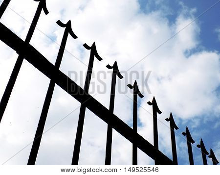 Spiky decorative iron fence and partly cloudy sky