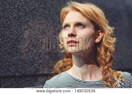 Ginger girl close-up near gray marble wall, tinted photo