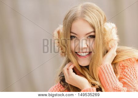 Smiling fashion woman in foggy fall autumn park. Happy attractive young girl in earmuffs sweater pullover and scarf. Happiness.