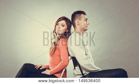 Young couple not talking to each other and sitting back to back after arguement. Disagreement in relationship. Man and woman get mad. Instagram filtered.
