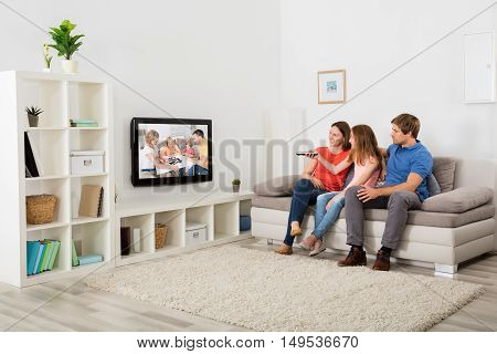 Family Sitting On Sofa Watching Television At Home
