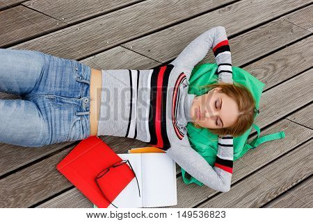 Student with books resting lying on wooden floor in street