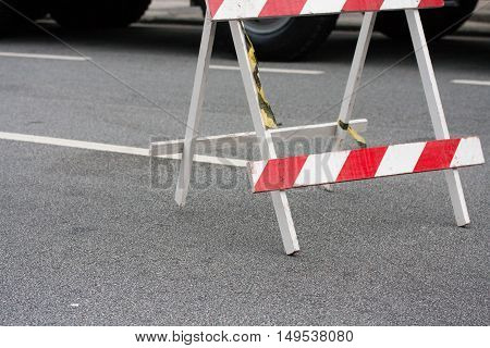 Traffic barrier trestle with yellow tape on street