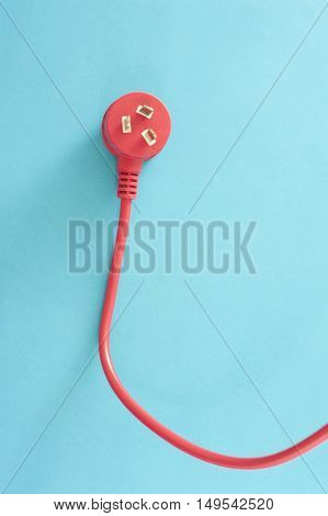 Red electrical lead with integrated three prong Australian plug on a blue background with copy space conceptual of power and energy