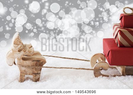 Moose Is Drawing A Sled With Red Gifts Or Presents In Snow. Christmas Card For Seasons Greetings. Silver Background With Stars And Bokeh Effect. Copy Space For Advertisement
