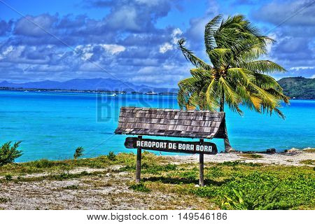 HDR image of Bora Bora airport sign. Beautiful palm and blue sea at the background. French Polynesia South Pacific Ocean.