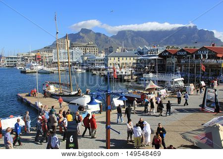 CAPE TOWN SOUTH AFRICA - NOVEMBER 24 2011 - Victoria and Alfred Waterfront harbor with recreation boats shops restaurants and Table Mountain on background in Cape Town South Africa.