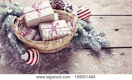 Christmas presents in basket fur tree and decorative balls on aged wooden background. Selective focus. Place for text. Toned image.