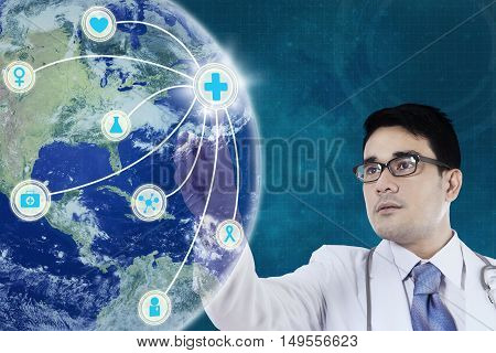 Young doctor is wearing glasses and his finger touching a globe medical network