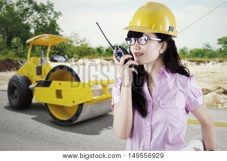 Beautiful contractor talking on the walkie talkie with a backhoe, shot outdoors