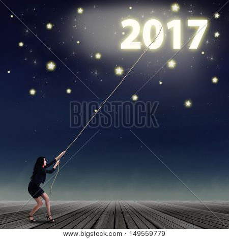 Woman try to pull number of 2017 between the stars from the sky night full of stars