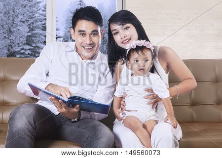 Young parents and their daughter smiling at the camera while reading book in the living room winter on the window