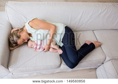 Mother sleeping with her baby in living room at home