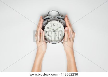 Female hands holding clock on white paper.