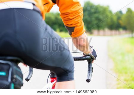 Man on race bike doing sport, cycling down country lane, view over shoulder from behind