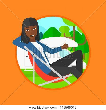 An african woman sitting in a chair and giving thumb up on the background of camper van. Woman enjoying vacation in camper van. Vector flat design illustration in the circle isolated on background.