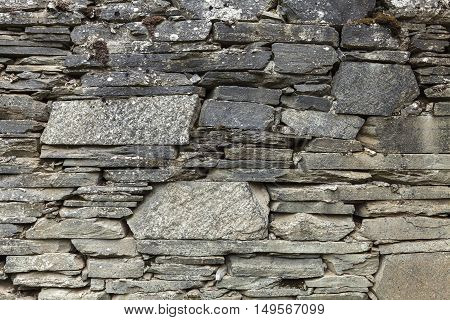 Exterior of slate stones wall. Abandoned buildings in rural area.