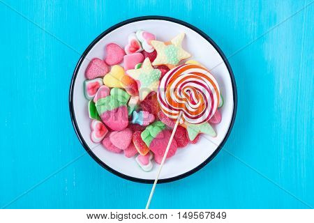 lollipop p and assorted jelly candies on a turquoise background