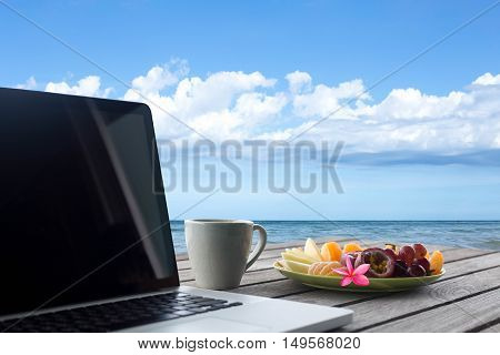 Selected focus mixes fruits and flower and laptop with coffee mug on wooden table top ocean view