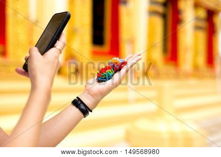 Woman taking photo of colorful fabric flower with mobile or cell phone