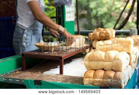 Pile of bread rolls with woman slicing in background in country style