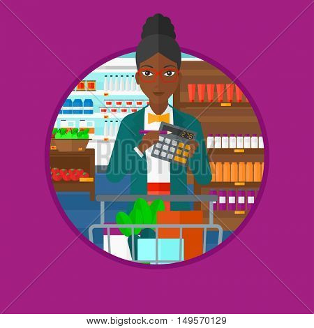 An african-american woman with calculator and supermarket trolley full with products. Woman checking prices with calculator. Vector flat design illustration in the circle isolated on background.