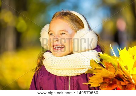 Happy little girl in earflaps with autumn leaves in the park