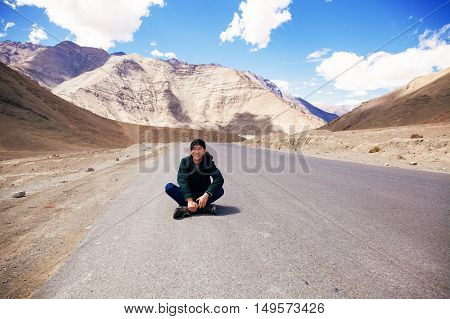 Young Asian Male Traveler Sitting In The Middle Of Empty Road With Freedom And Joy In Leh, Ladakh, I