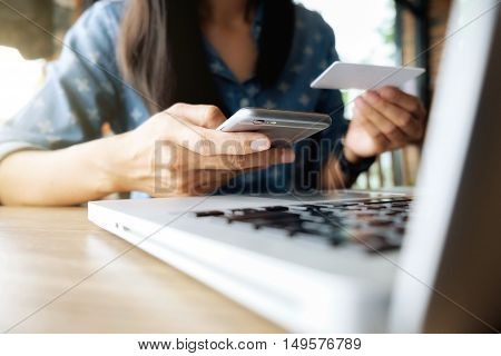 Beautiful young asian woman using smartphone and holding card for shopping online payment at coffee shop. Shopping concept with copy space. Online shopping concept.